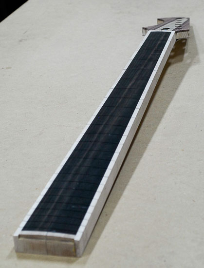 Compound radius on an ebony fretboard of a six-string bass neck