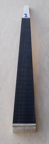 Low angle shot of an ebony fretboard on a bass guitar neck blank