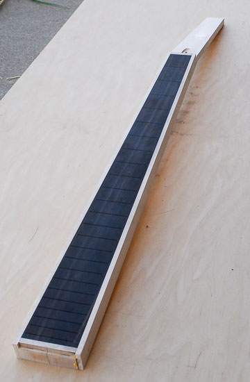 Black bass guitar neck with white stripes down either side