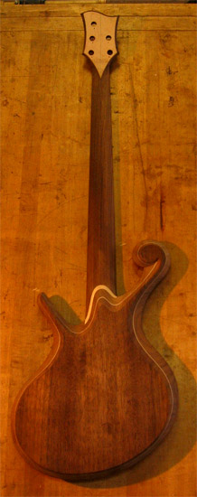 Black walnut back of a fretless custom bass