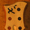 Xylem logo on a curly maple bass headstock